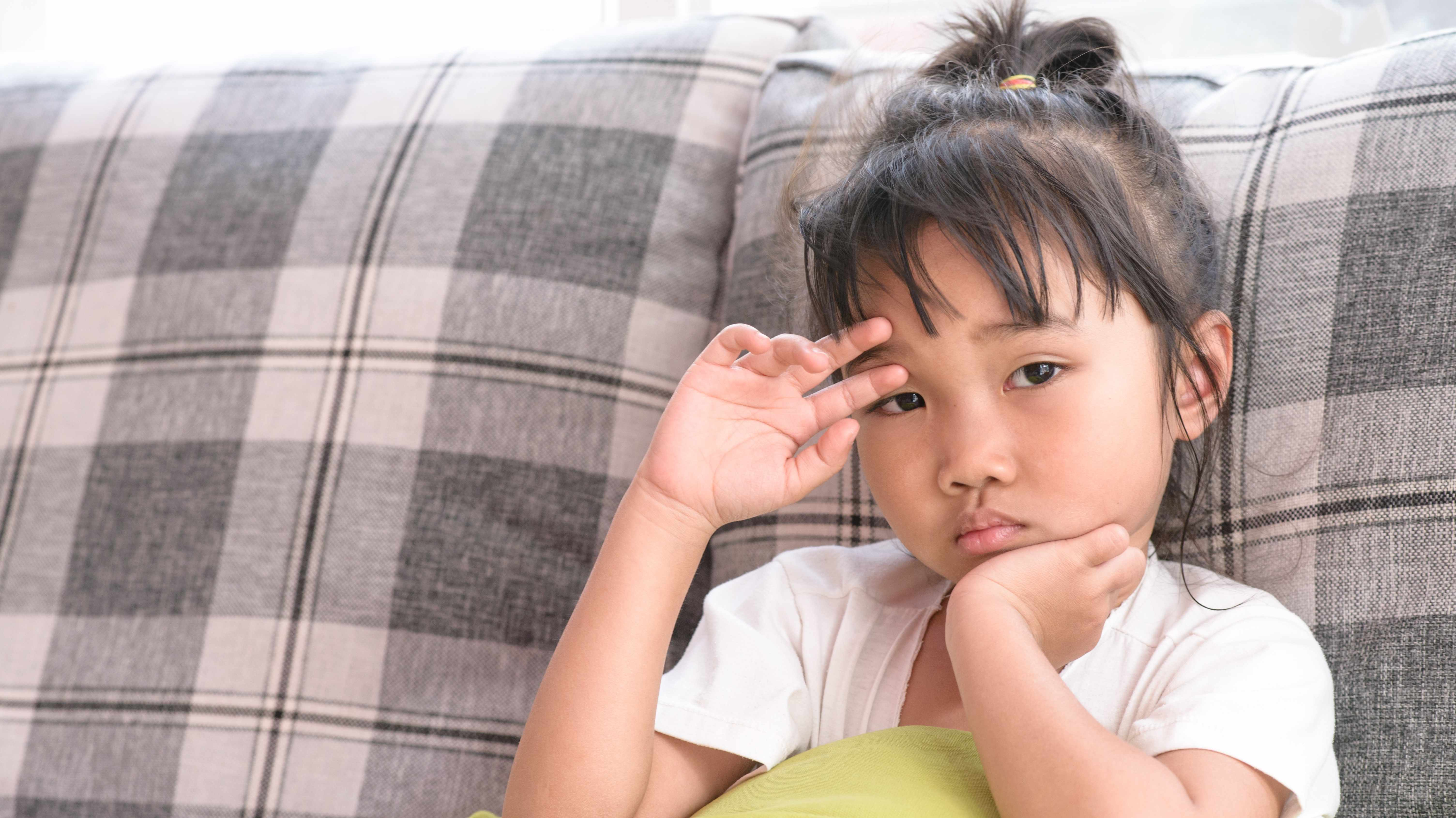 a young girl sitting on a couch, looking sad, worried or sick
