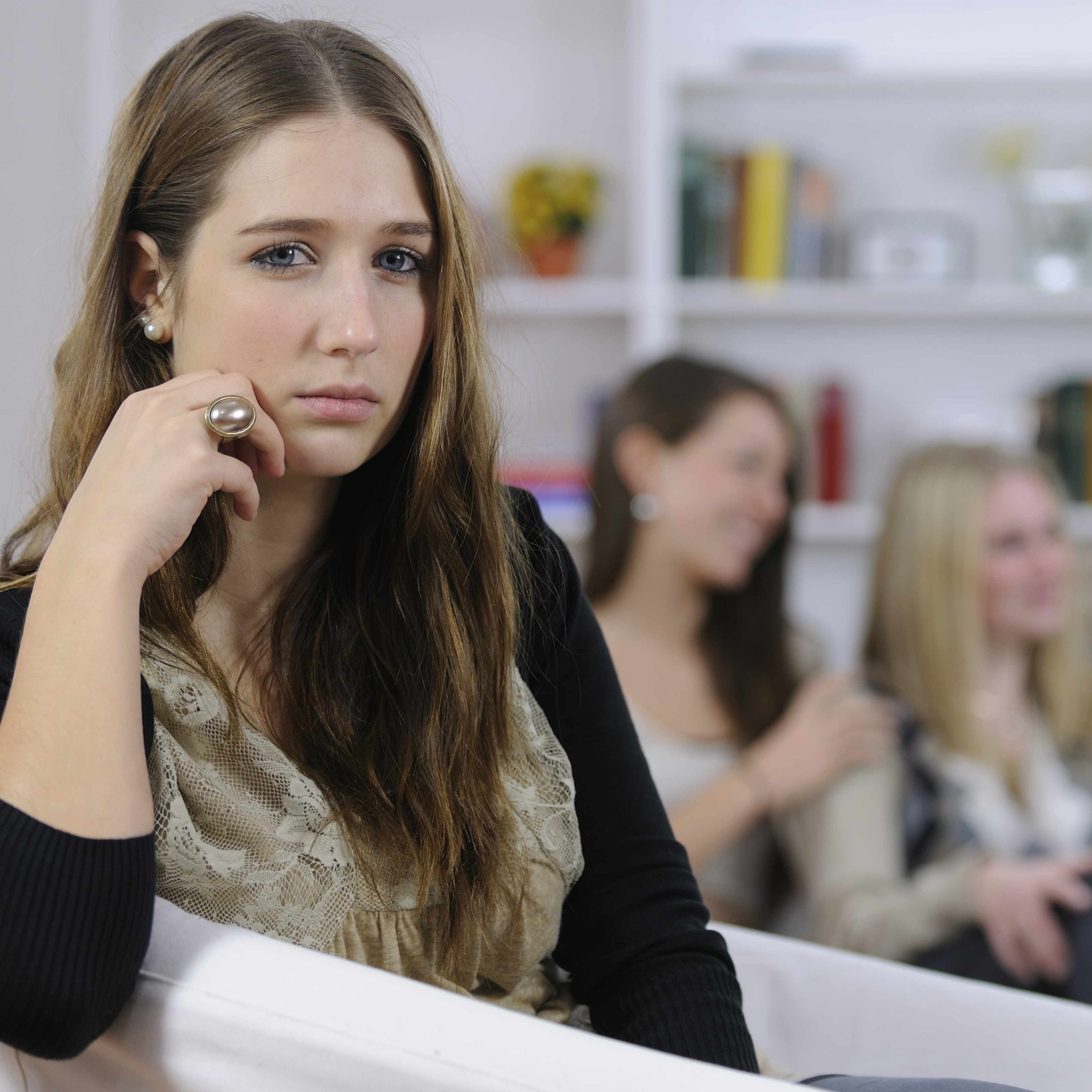 a young girl sitting on a couch sad, upset about being left out friends in background talking
