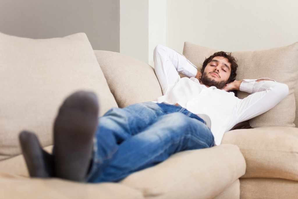 a young man stretched out on a couch, napping