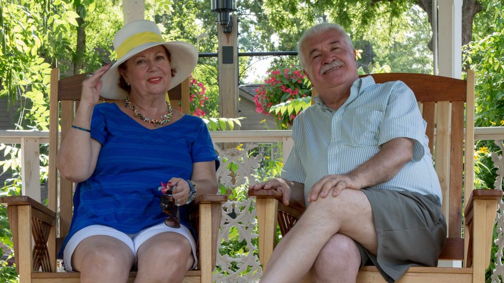 an older woman and man sitting together in a gazebo