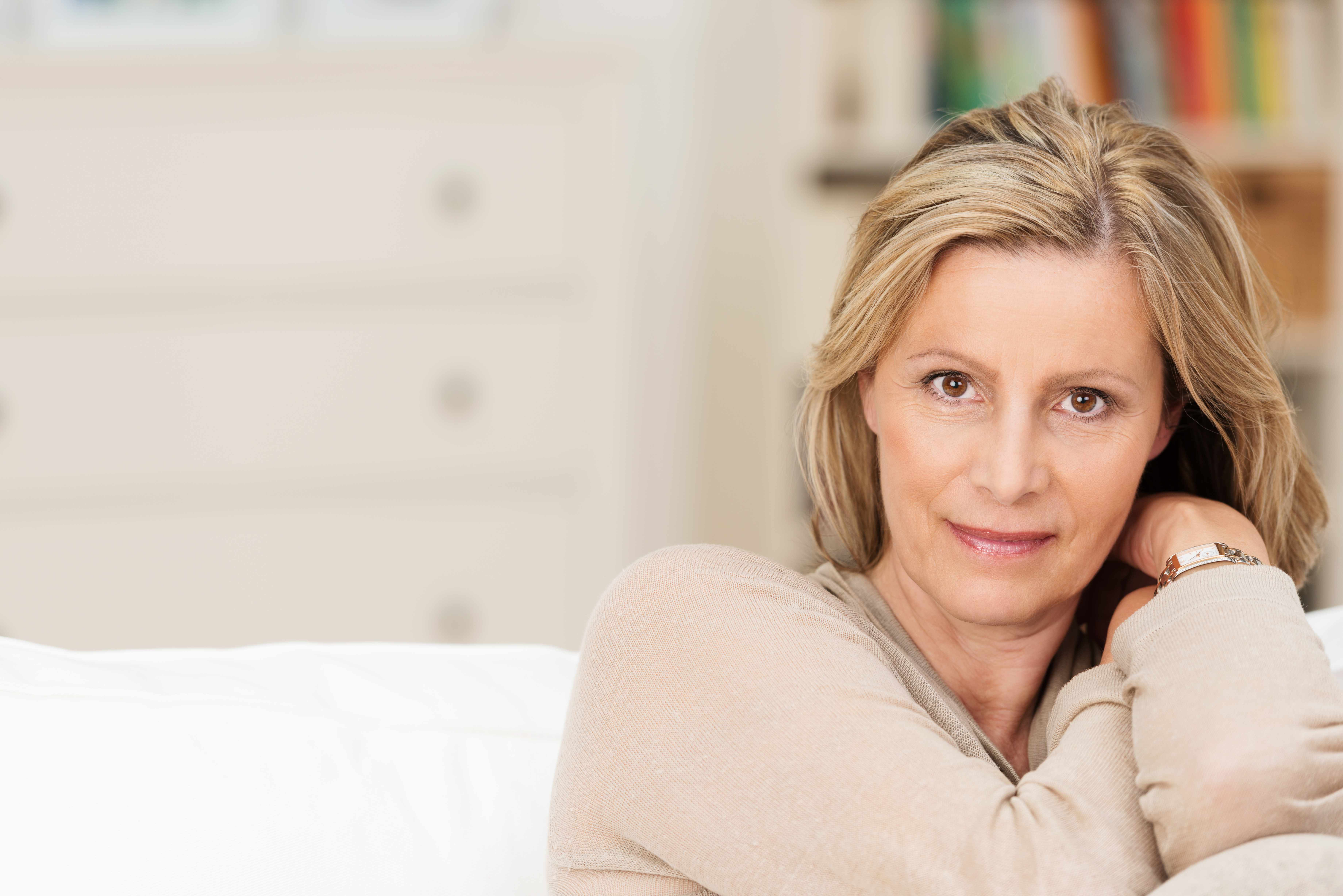 close-up of a serious-looking middle-aged woman sitting on a couch