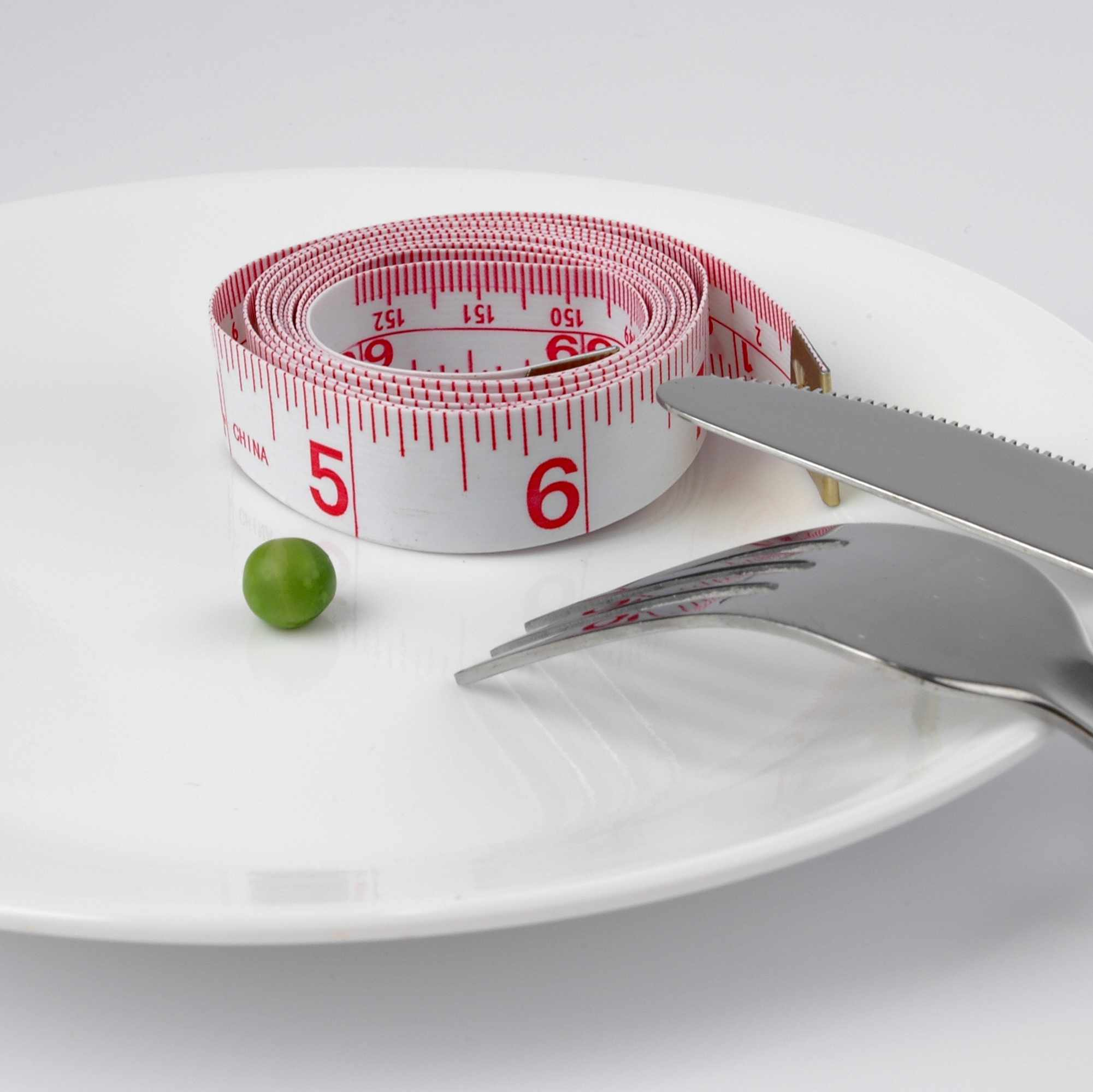empty plate with tape measure and one pea representing eating disorder