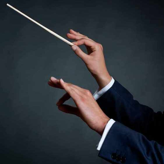 male orchestra conductor directing with his baton in concert
