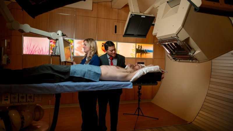 Personal médico y un paciente durante el proceso de la terapia con rayo de protones