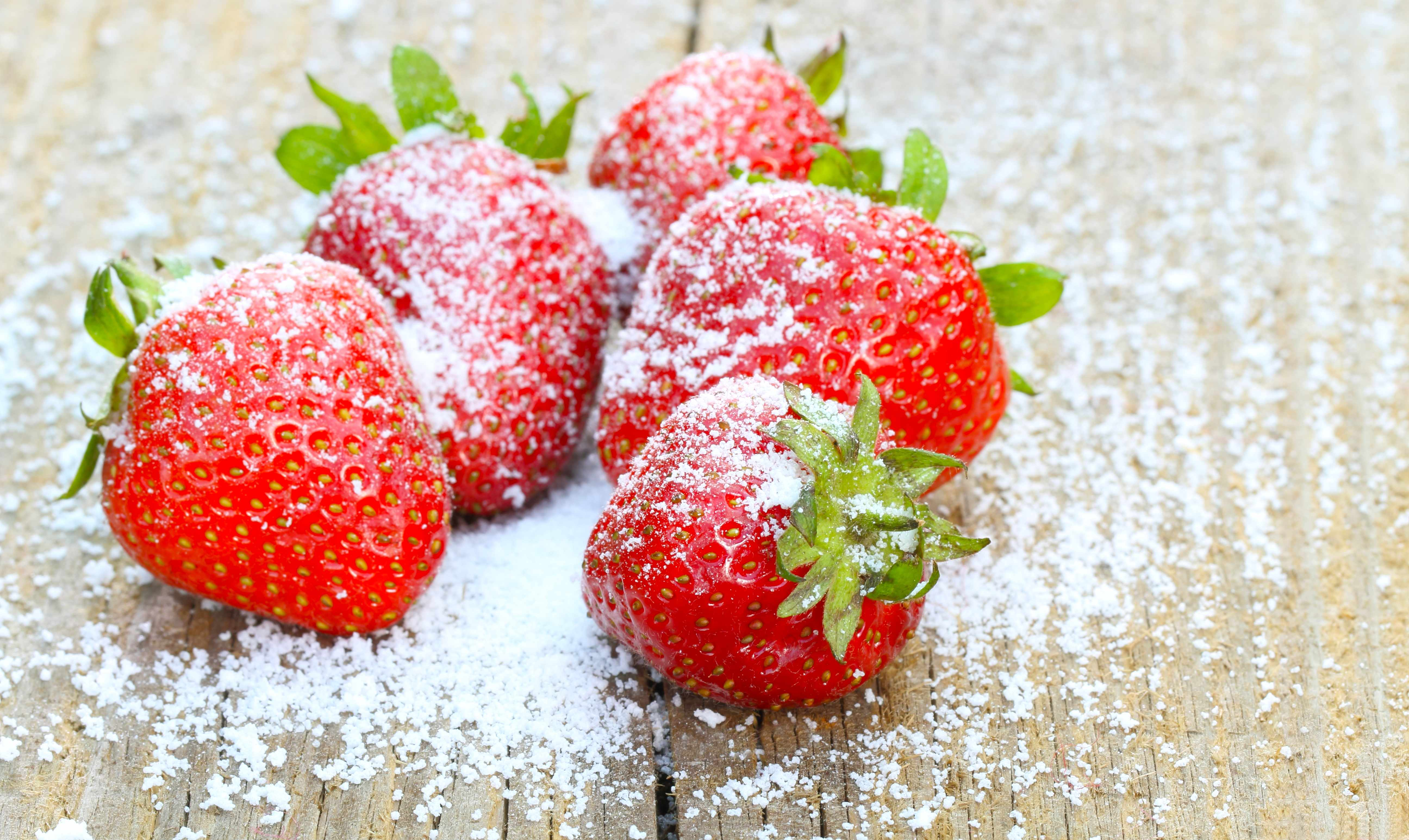 fresh strawberries on a table with sprinkled sugar