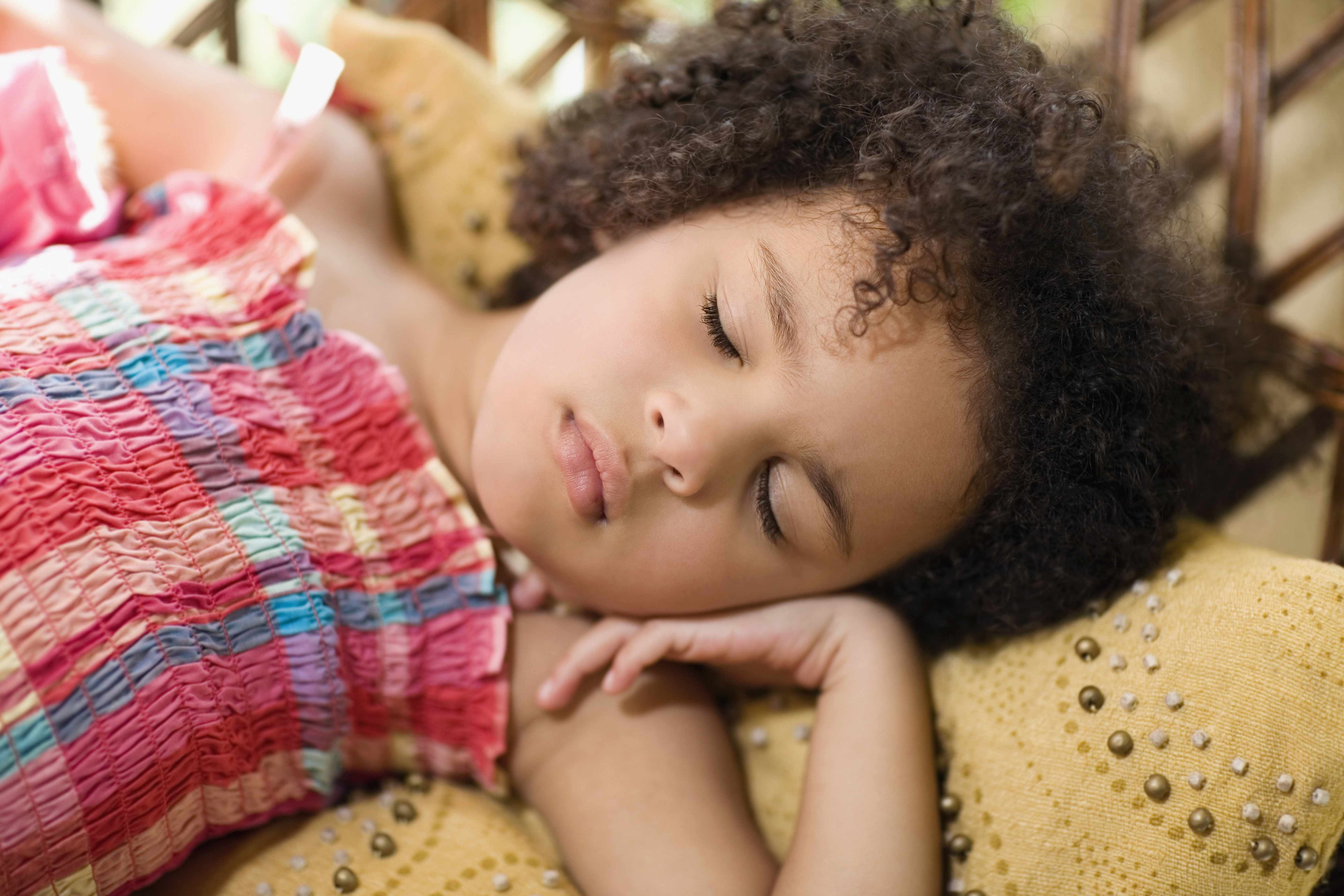 a little girl in a sundress sleeping or napping on a bed