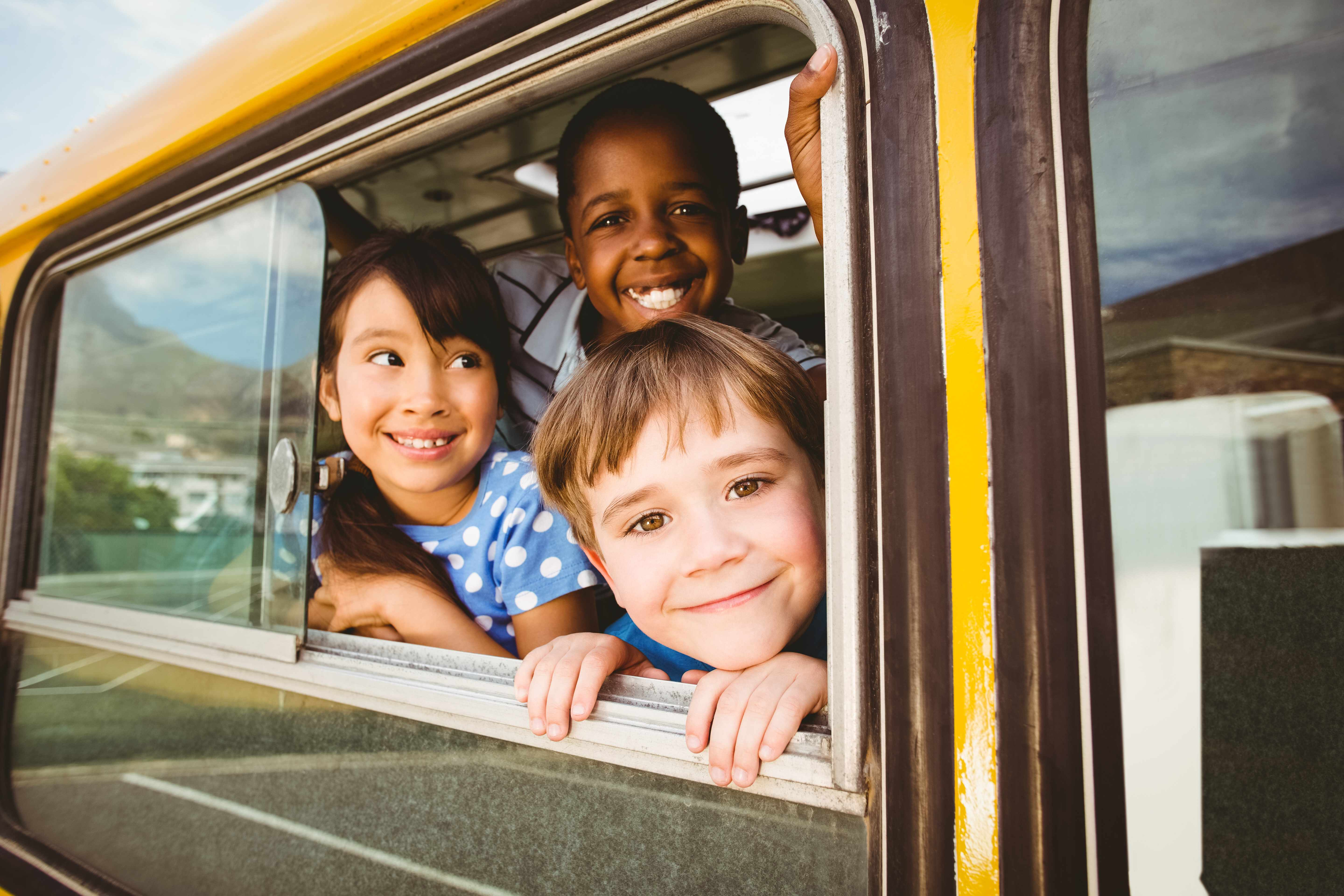 three children smiling and leaning out a school bus window