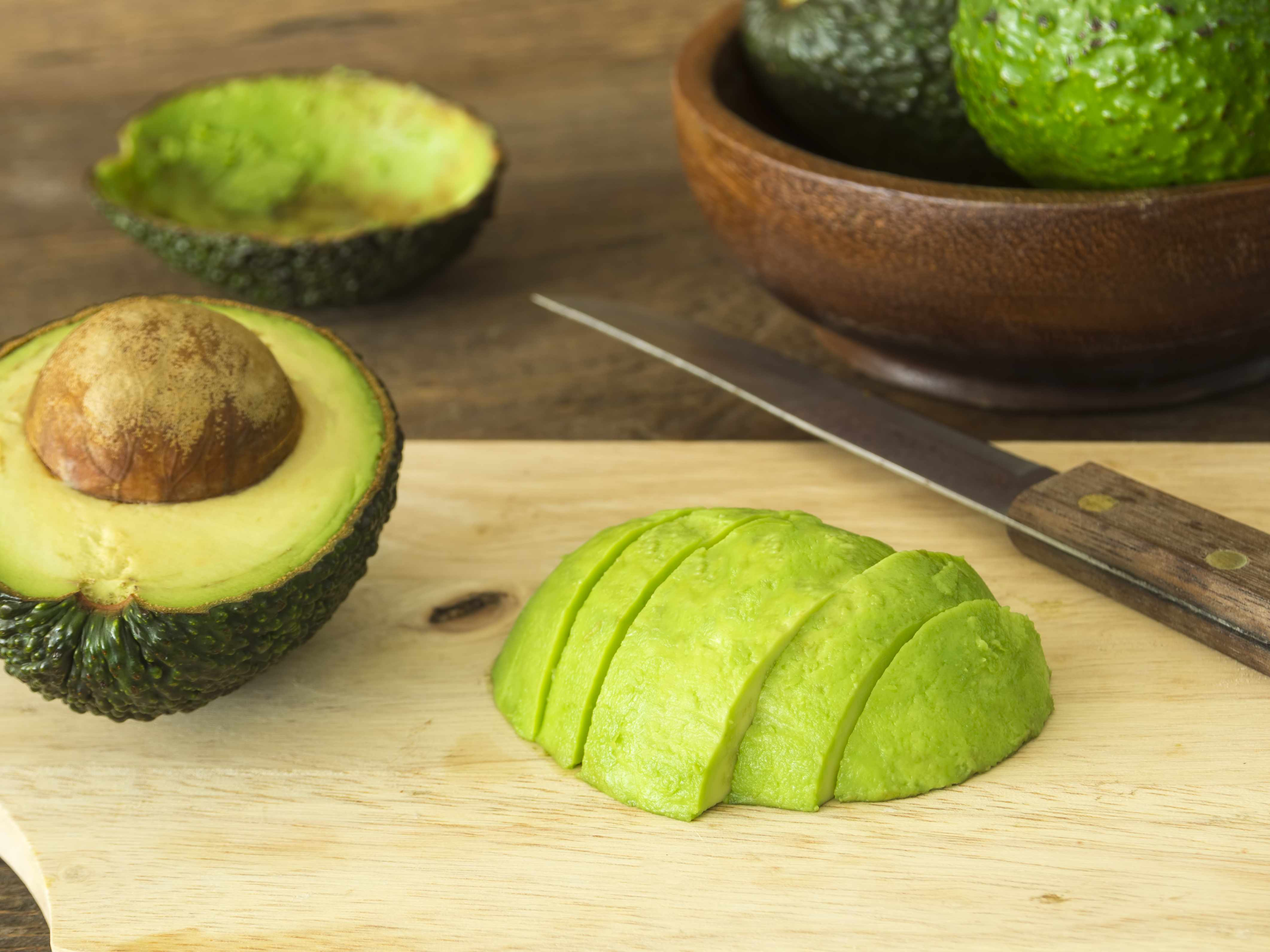 a knife and sliced avocado on a wooden carving board
