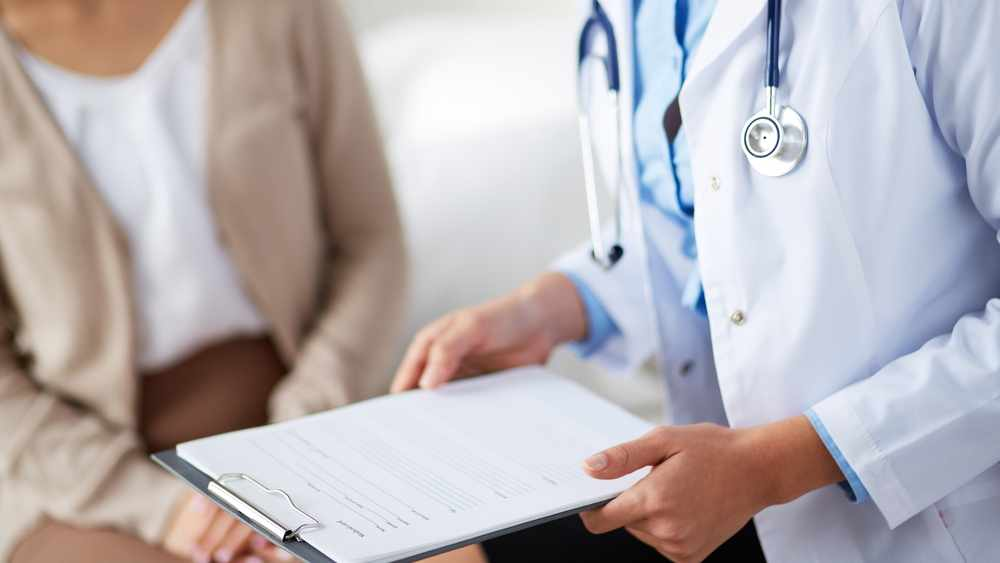 Doctor holding application form while consulting patient