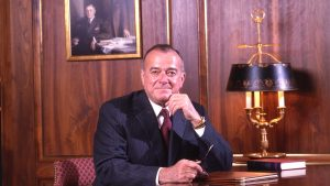 Male sitting at a dark wood desk looking toward the viewer dressed in a pinstriped suit, with his hand near his chin