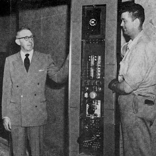 a 1956 photograph of General Service's Clyde Crume and a Westinghouse elevator installer at work in a new patient elevator