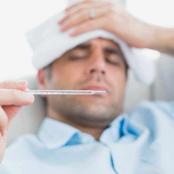 a sick man with cold or flu lying on sofa checking his temperature for a fever