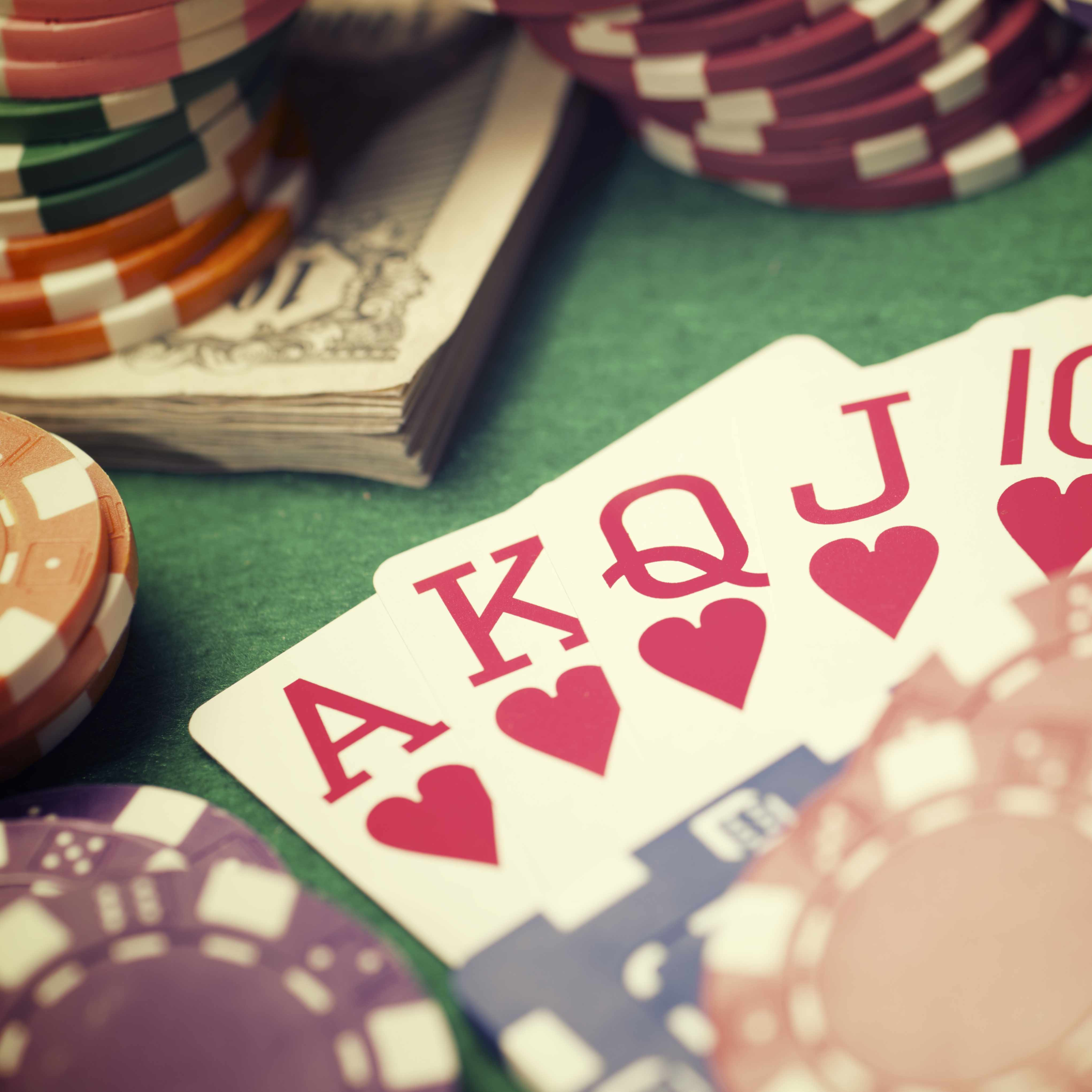 a close-up of playing cards, money and poker chips on a gaming table