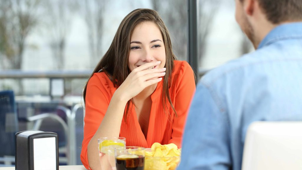 a couple sitting at a table and woman covering her mouth because of bad breath