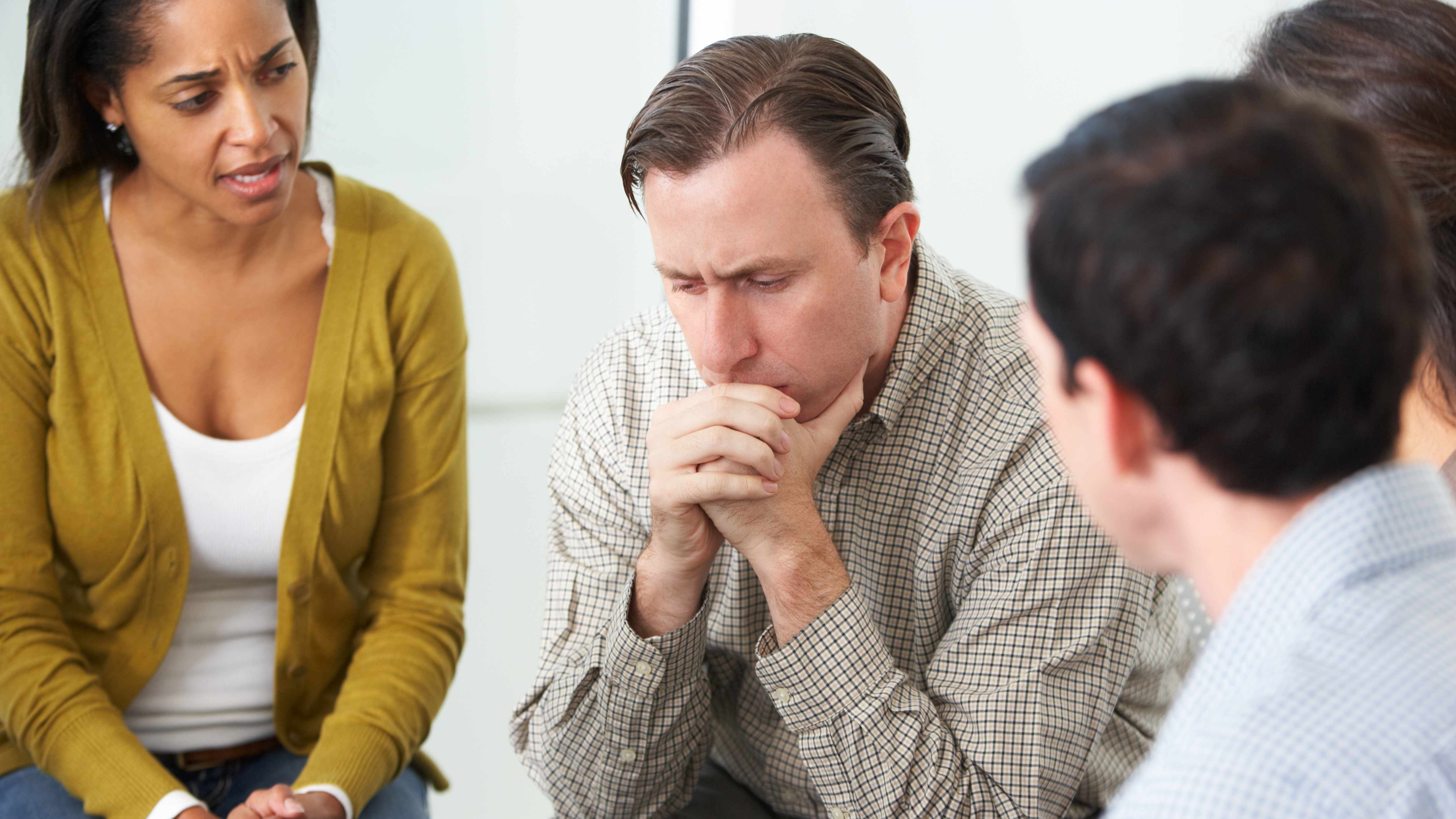 a man in a counselling session looking sad and depressed with concerned people sitting around him