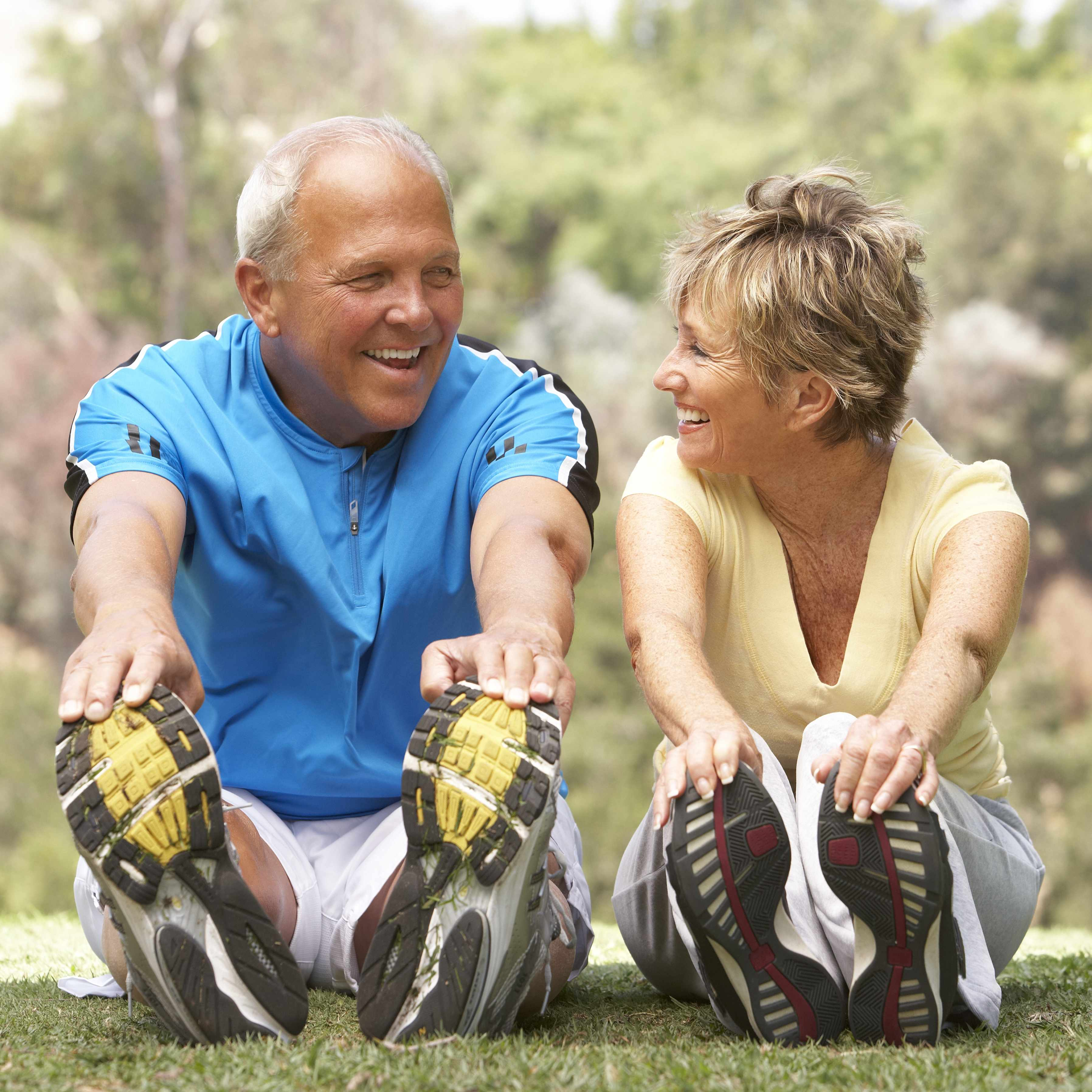 a middle-aged man and woman smiling and exercising in the park