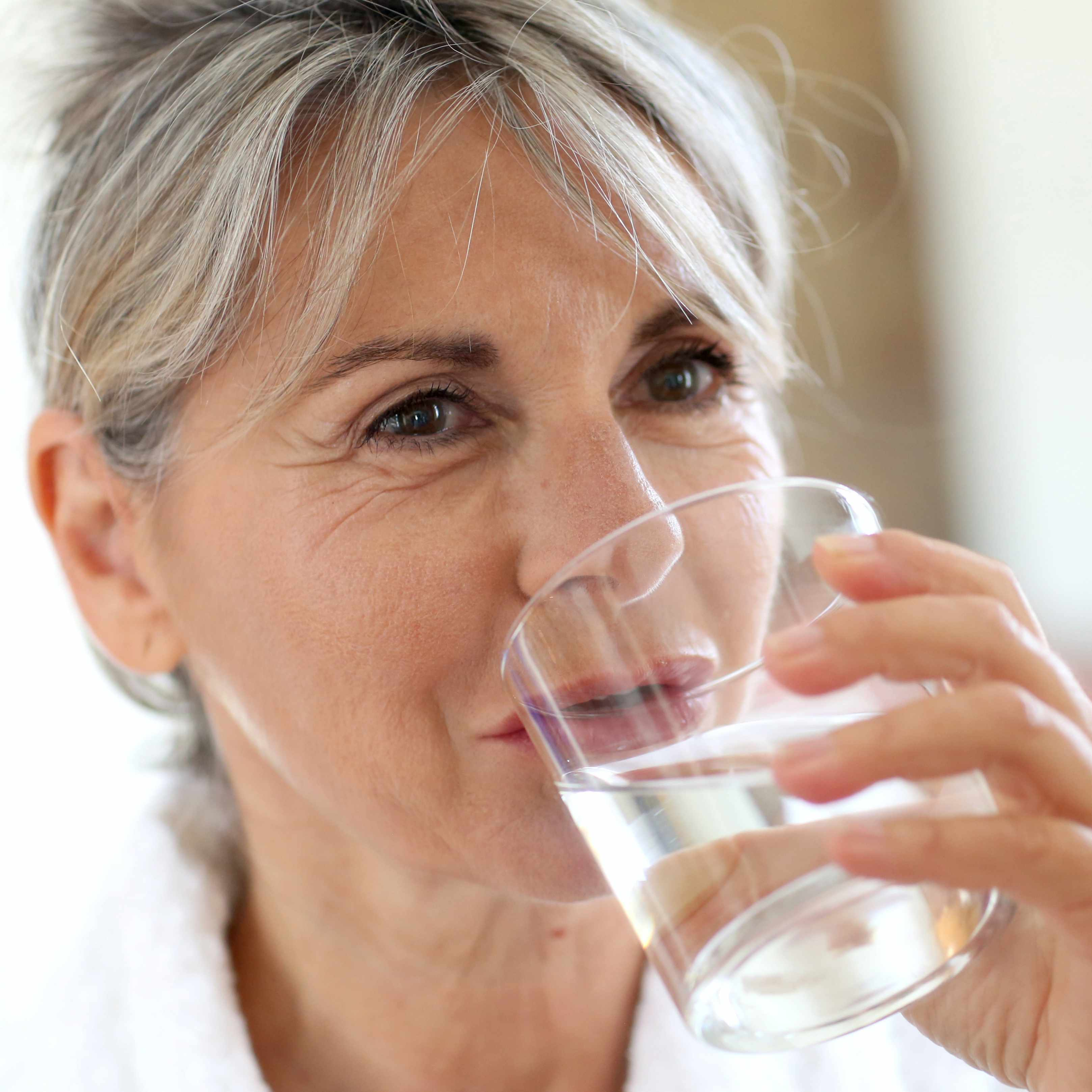 a middle-aged woman drinking a glass of water to stay hydrated