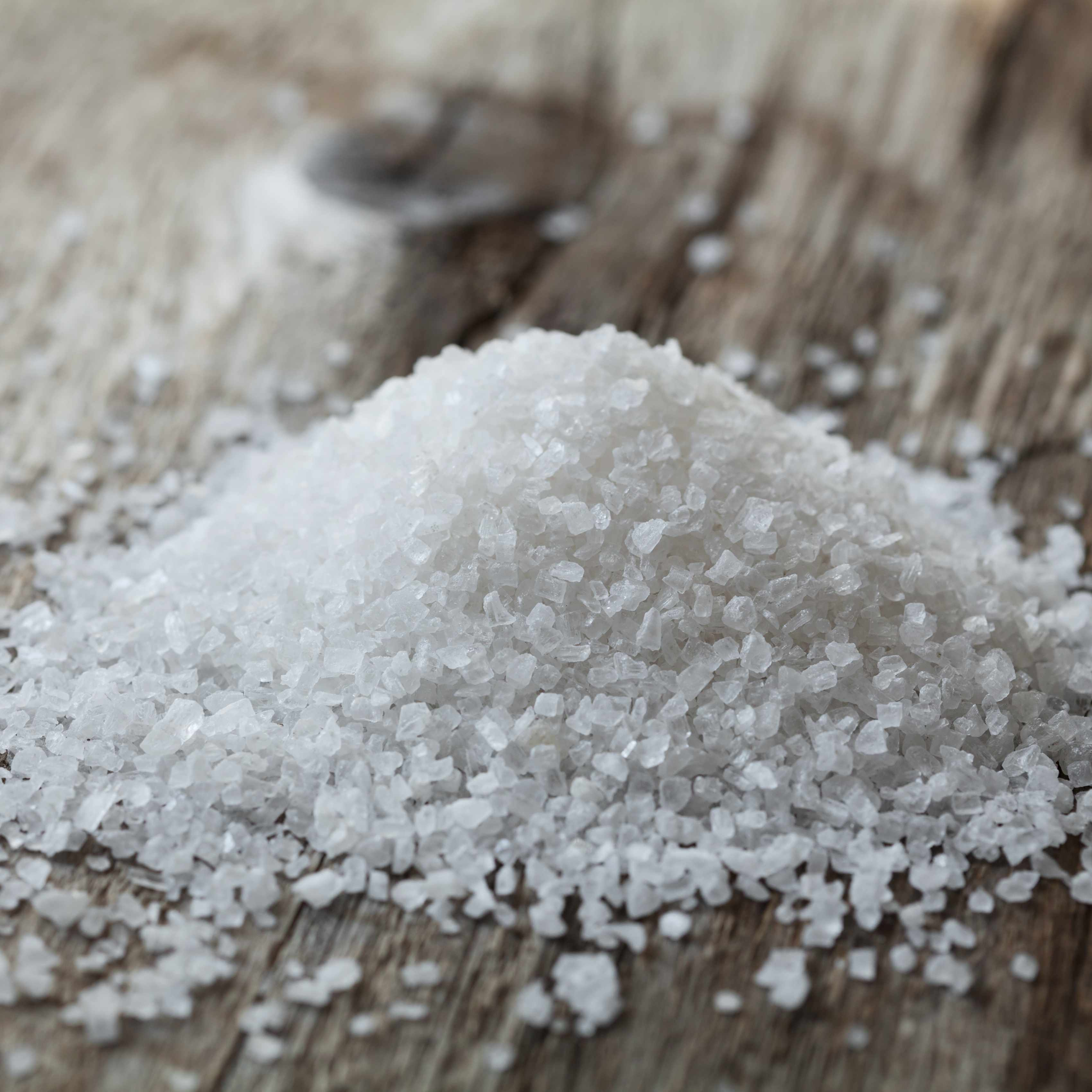 a pile of sea salt on a weathered wooden surface