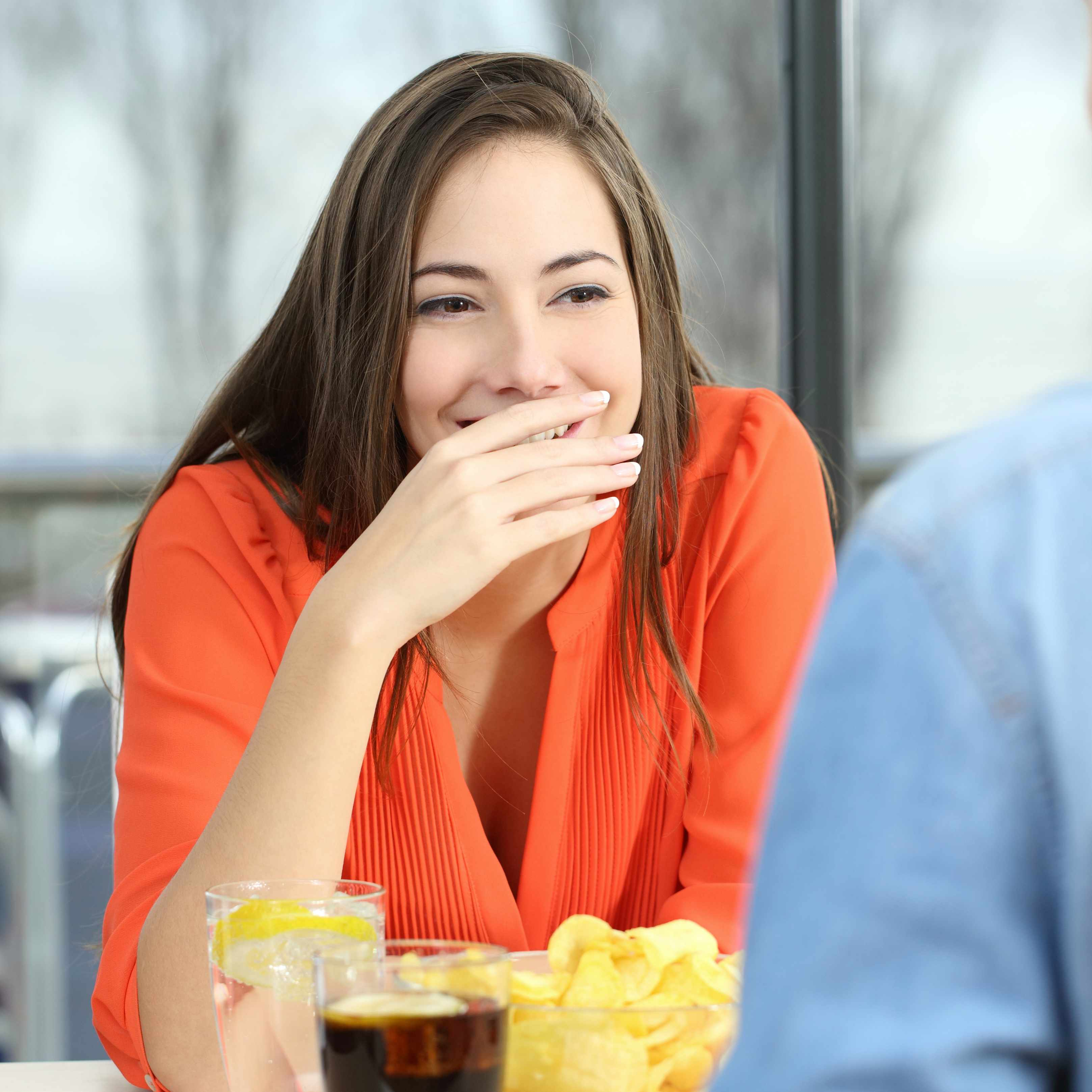 a woman sitting at a table covering her mouth because of bad breath