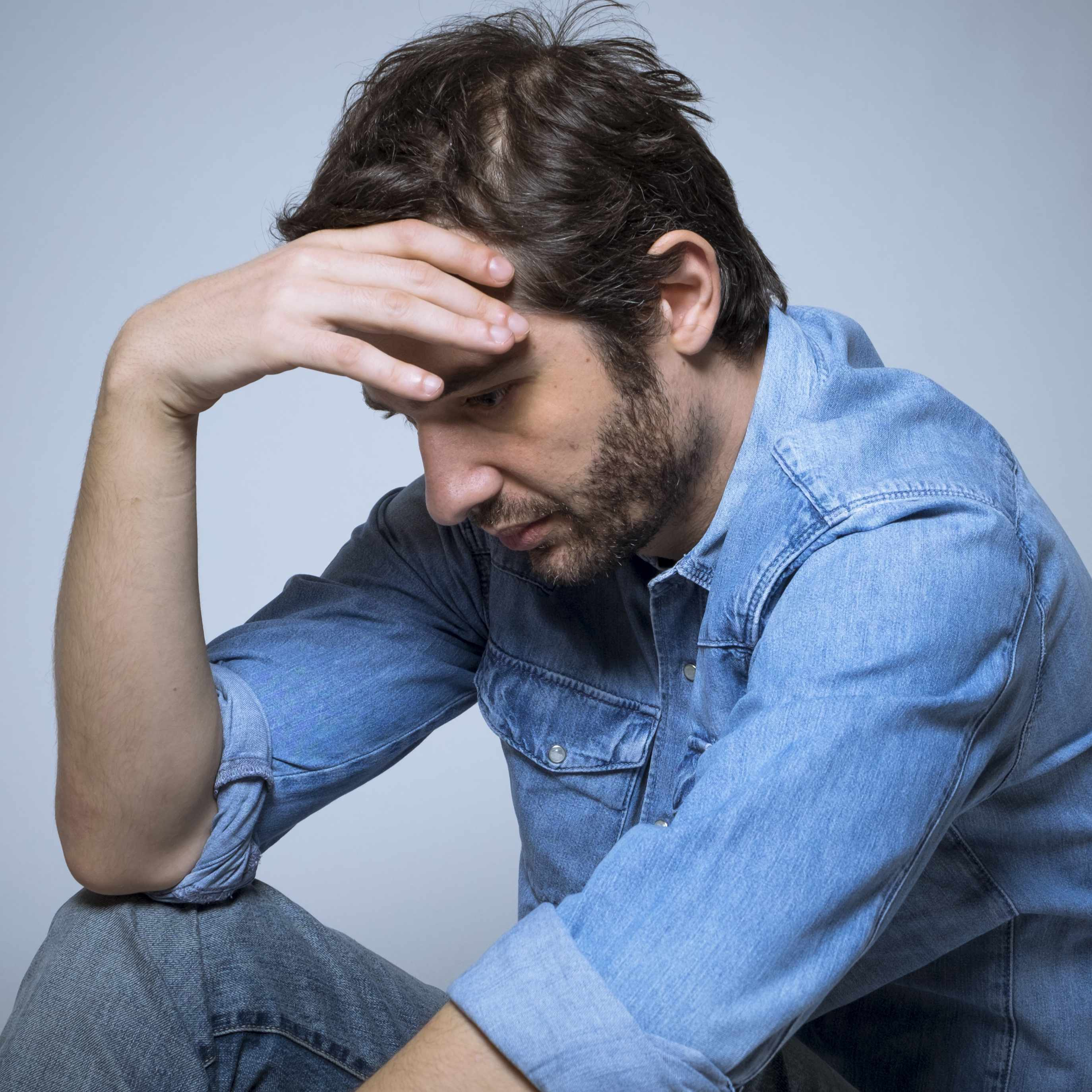 a young man depressed holding his head