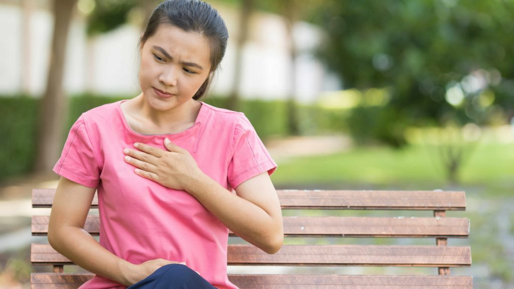 Una mujer joven y sentada en la banca de un parque se sostiene el pecho porque siente acidez estomacal o molestias