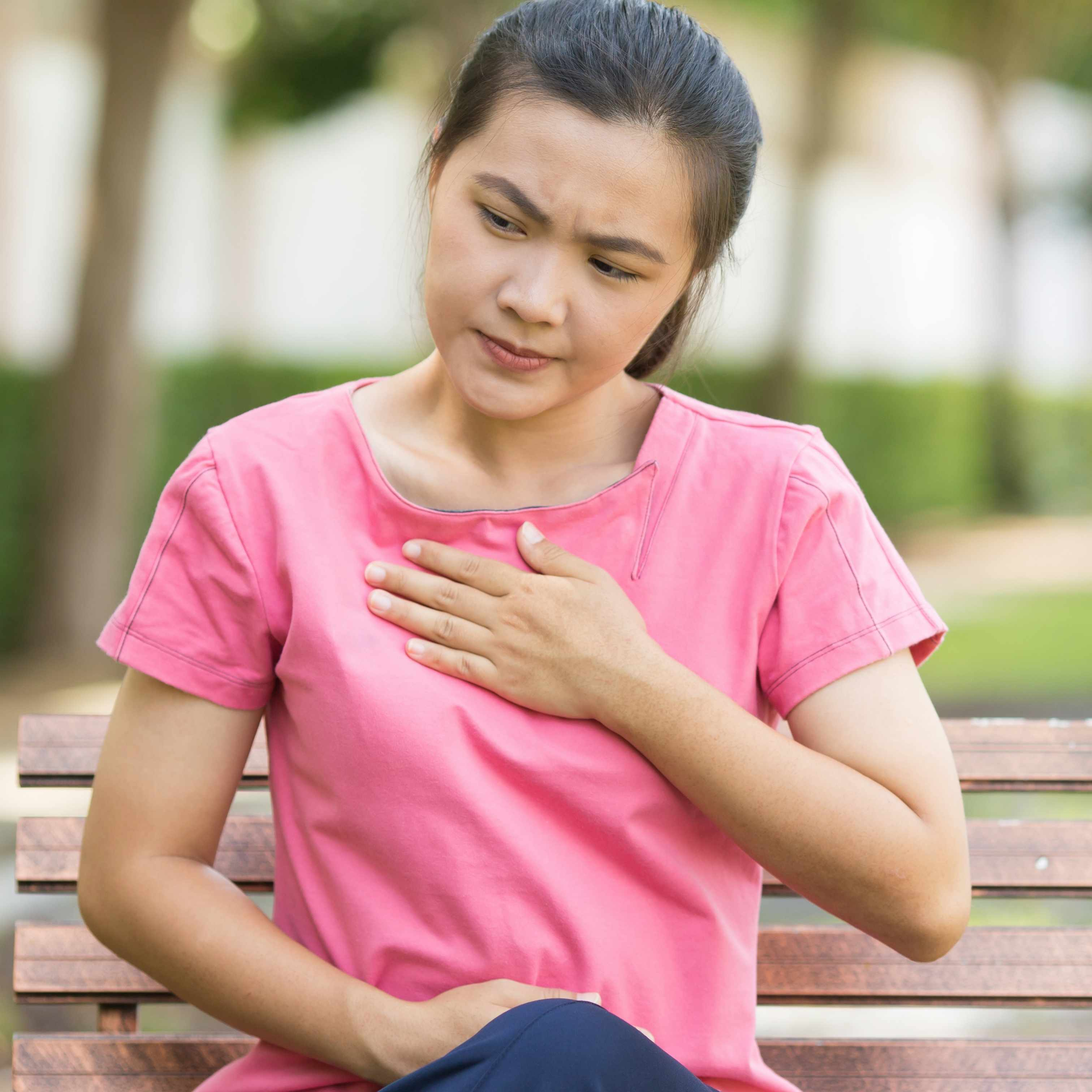 a young woman sitting on a park bench holding her chest because of heartburn or discomfort