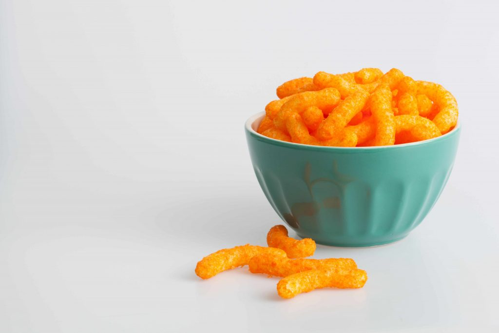 cheese puffs in a bowl and spilled onto the table