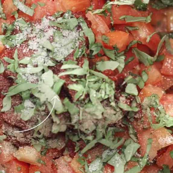 close up of sliced tomatoes and basil for pesto sauce