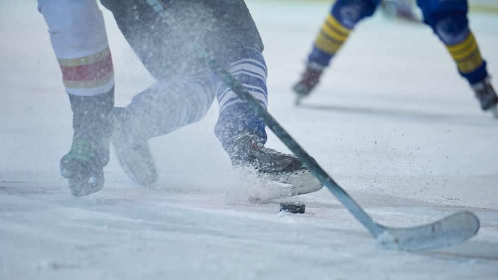 Jugadores de hockey en hielo con los palos y el disco