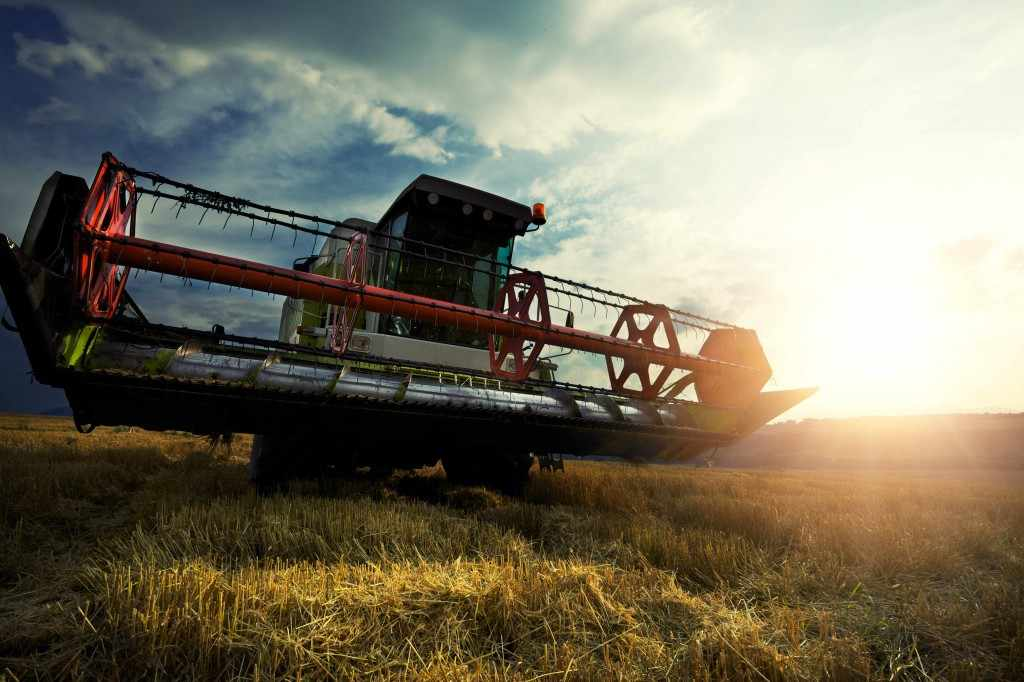 harvesting farm equipment in field with sun in background