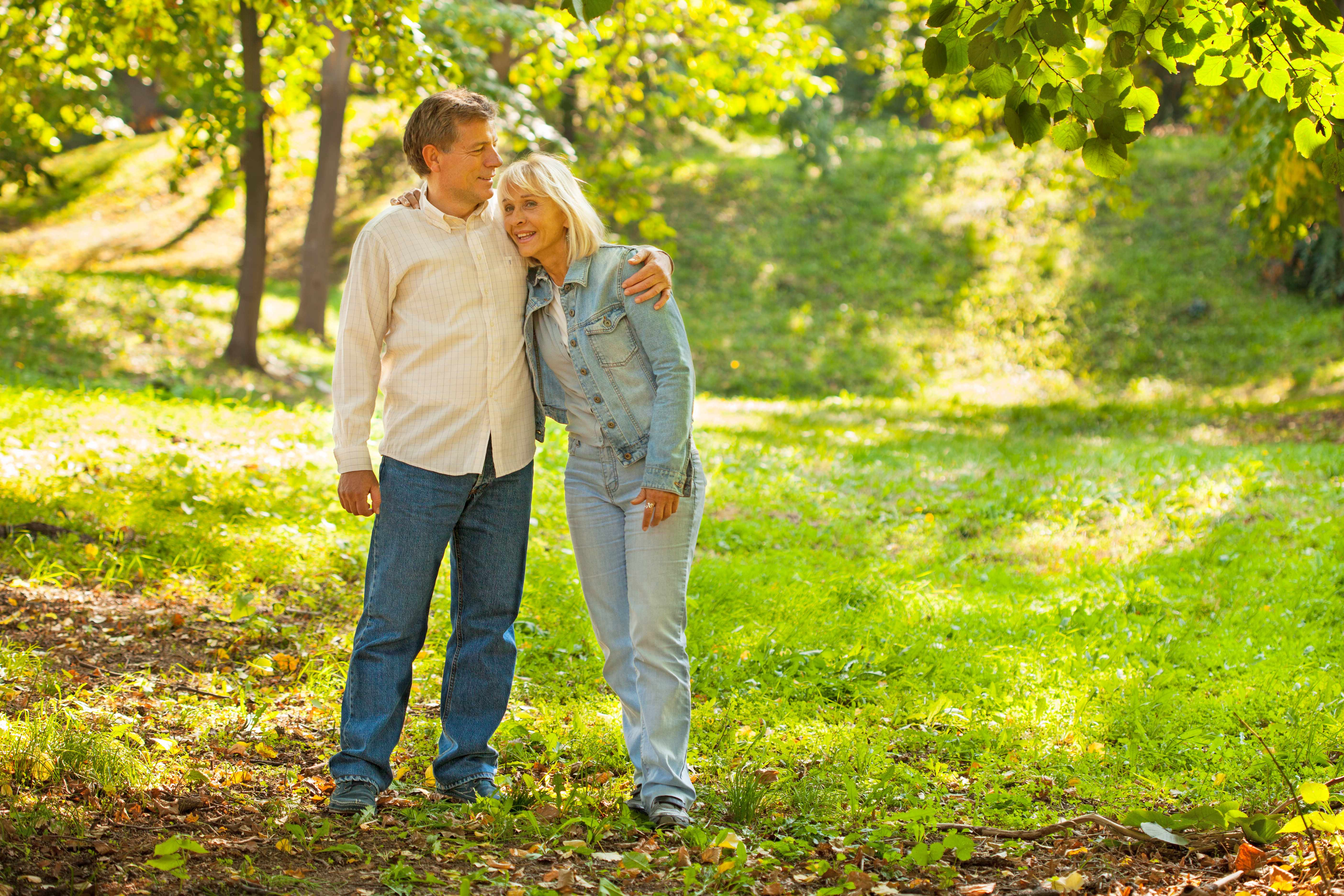 middle aged couple walking in a park together, arm in arm