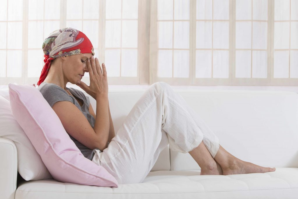 a woman with a head scarf sitting quietly on a couch with her hand together, deep in thought looking sad, perhaps praying
