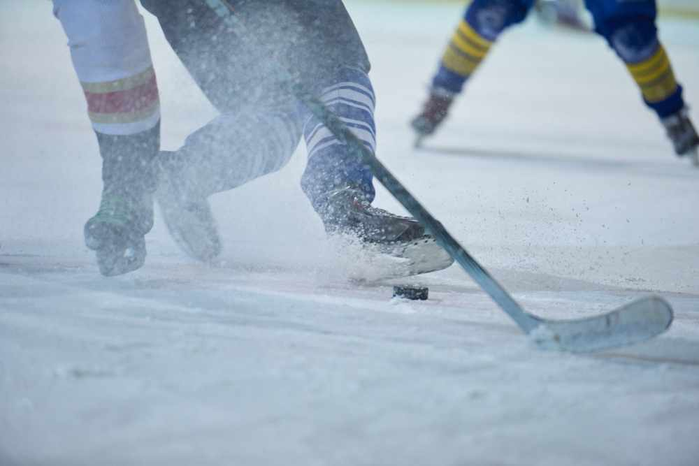 ice hockey players in action with hockey sticks and puck