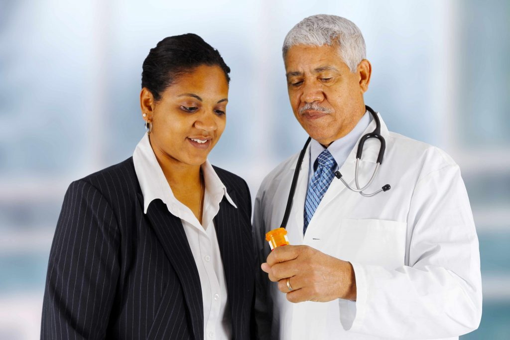 a pharmacist or medical staff person holding prescription medicine bottle while talking to patient
