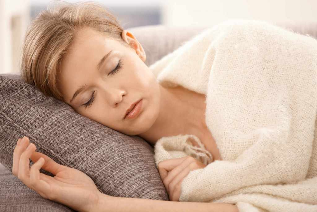 young woman sleeping napping on a a couch