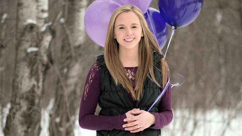 brain patient Nikki in the woods holding purple balloons