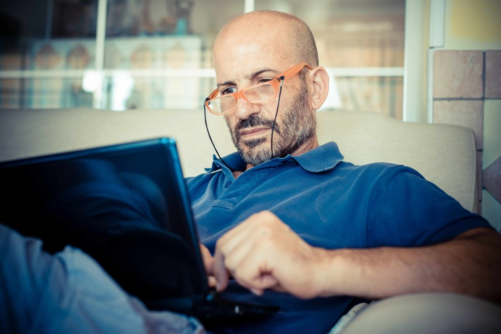 a bald middle aged man with glasses, sitting on a couch, looking at a laptop screen