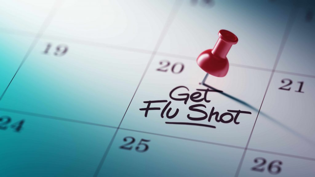 a close-up of a calendar, with a red push pin and the words GET FLU SHOT written on one date square