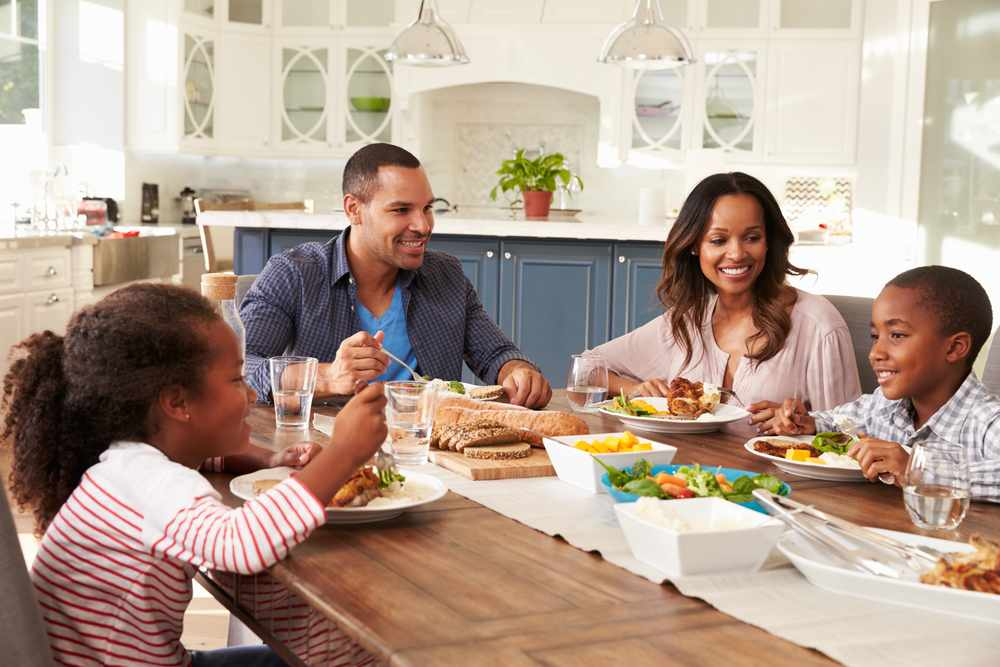 a-family-at-the-breakfast-table-smiling-at-one-another-and-enjoying-healthy-food-original