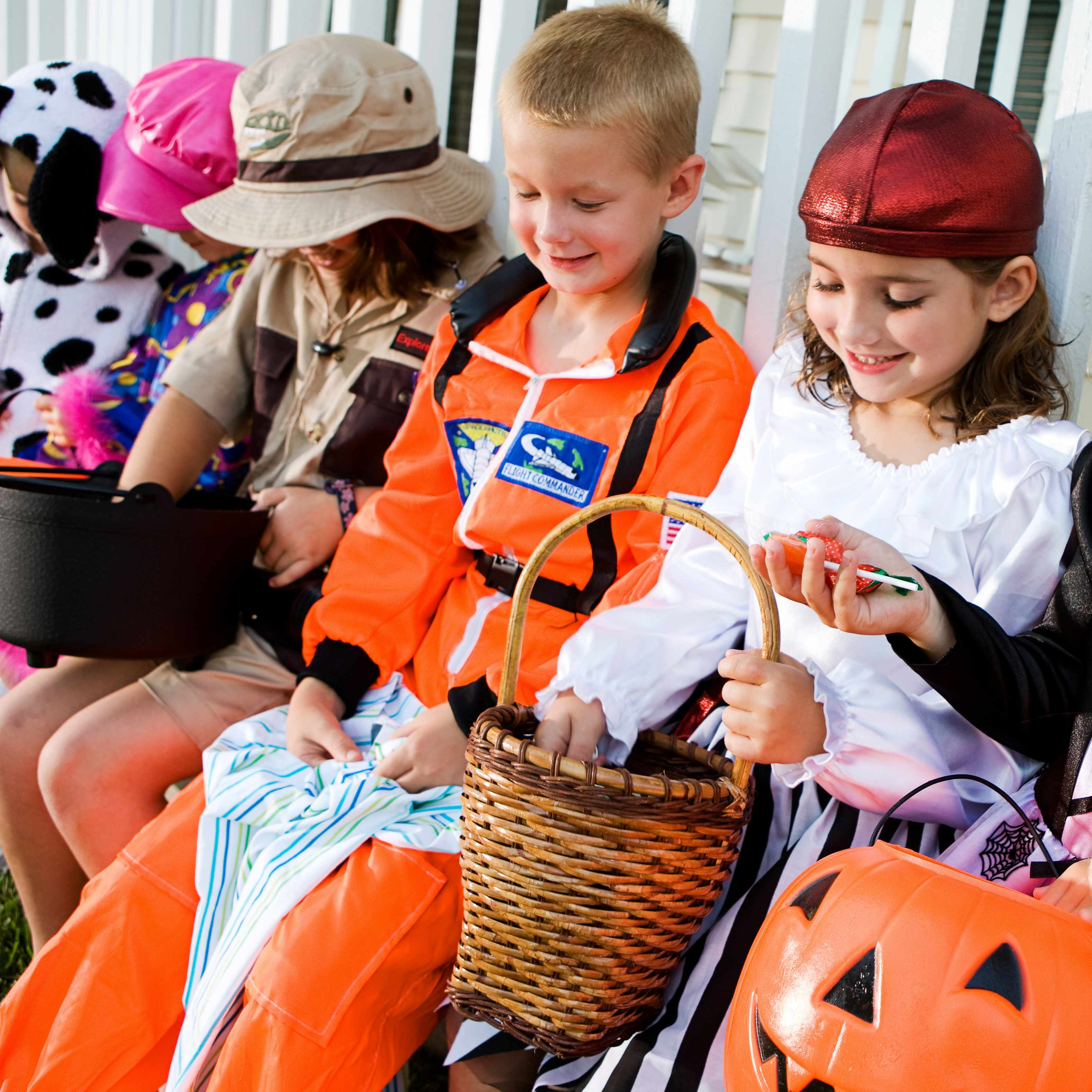 a group of children in Halloween costumes sitting on a bench looking at their candy and treats