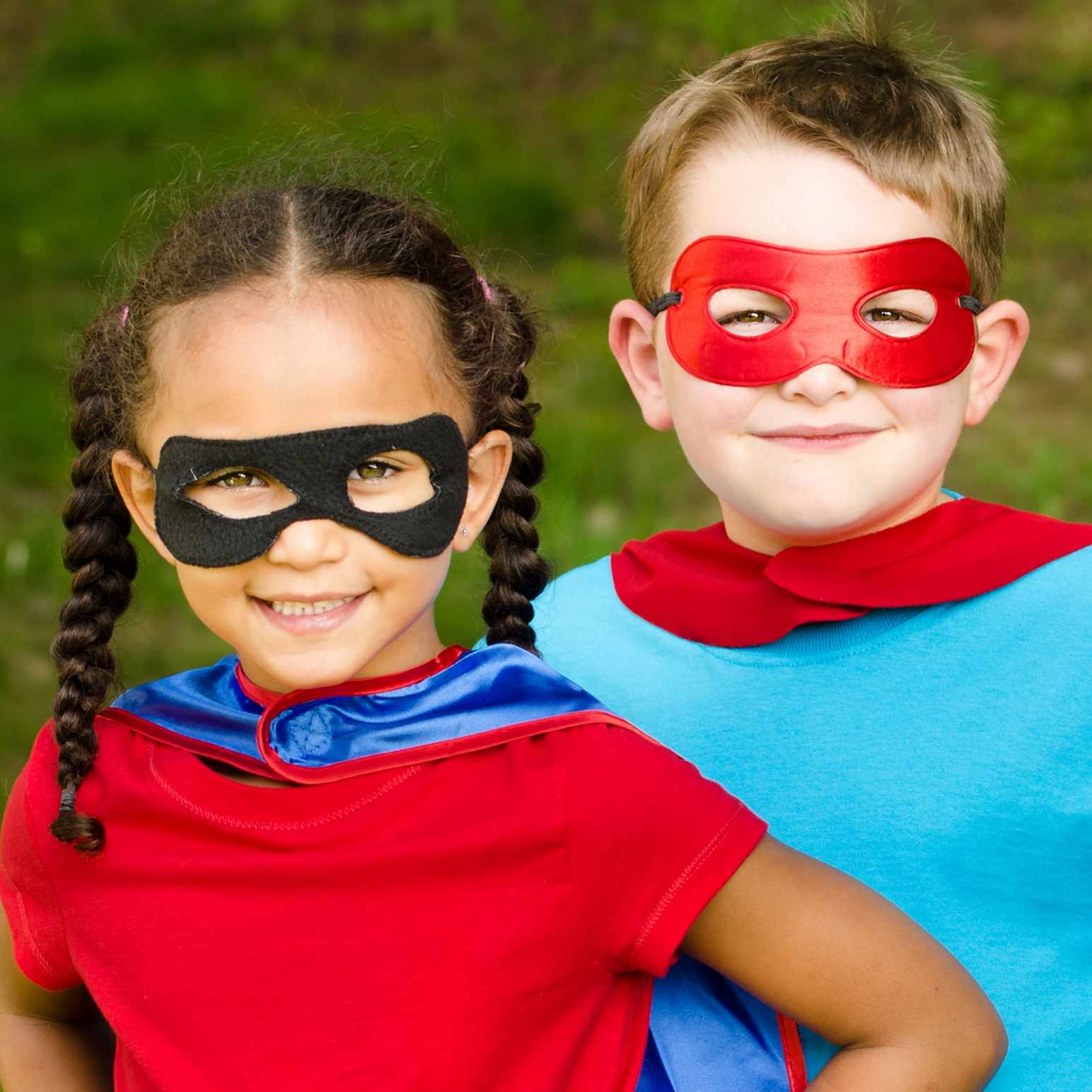a little girl and a little boy dressed up in costumes as superheroes with masks