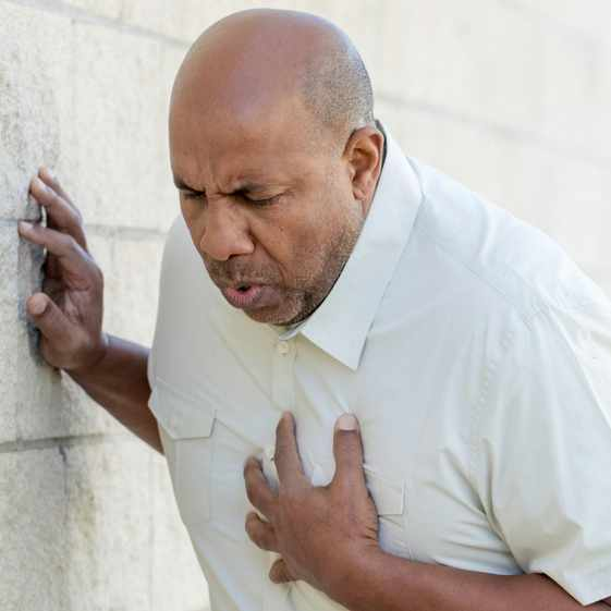 a middle-aged African American man holding his chest and leaning against a wall, maybe a heart attach or stroke