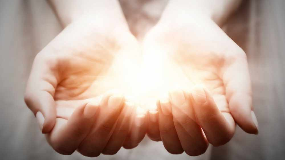 a-woman-holding-a-bright-shining-light-in-the-palm-of-her-hands-16x9
