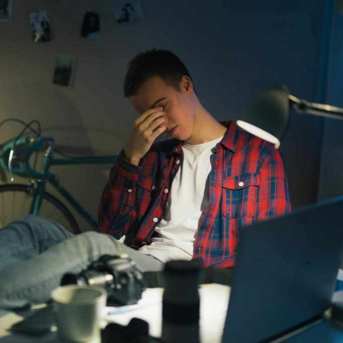 a young teen or college student sitting at his computer rubbing his eyes tired and exhausted