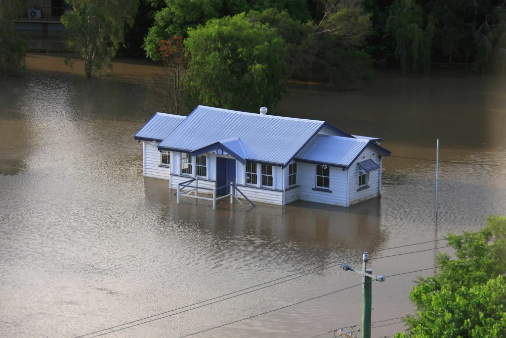 an arial view of a house completely surrounded by flood waters