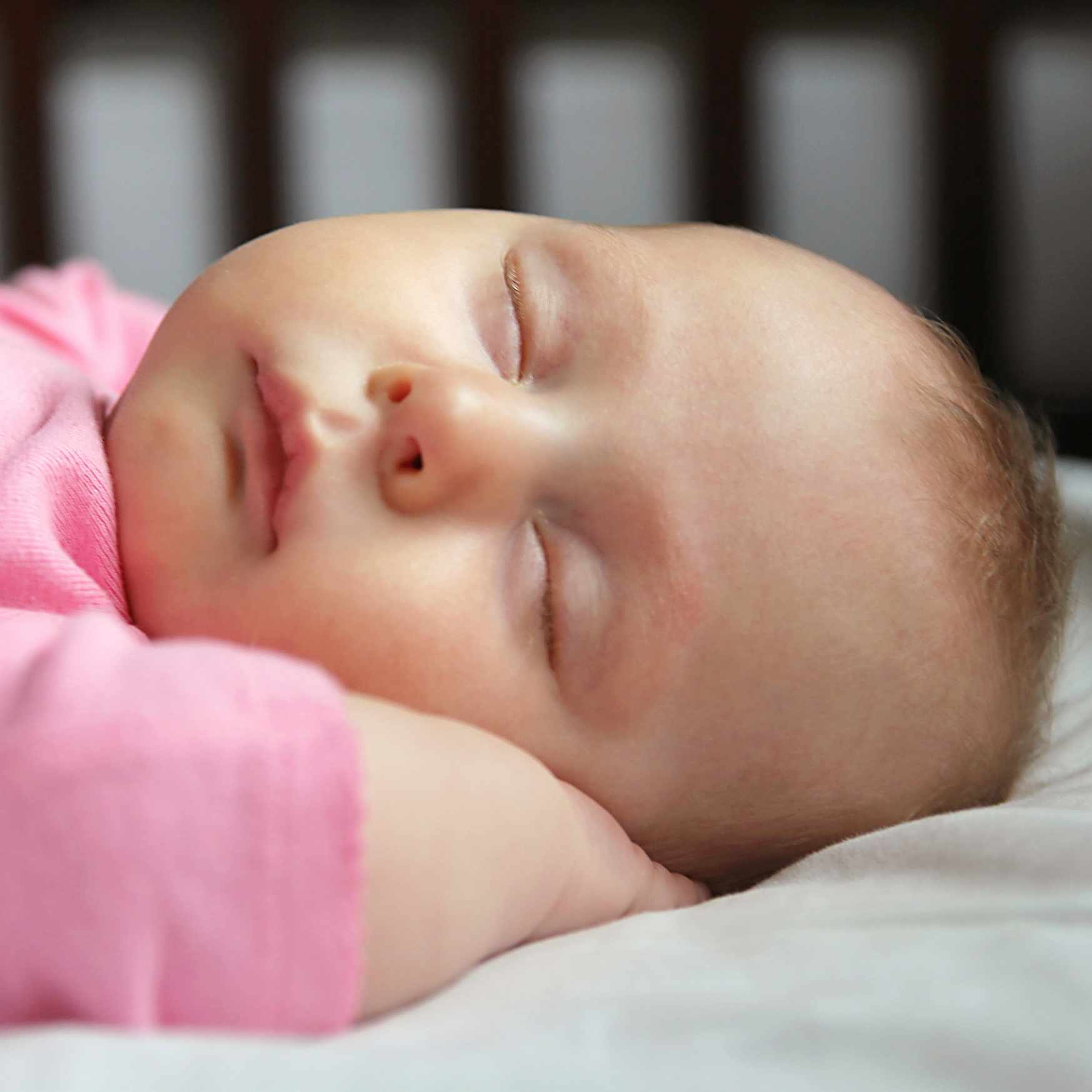 baby girl asleep on her back in a crib