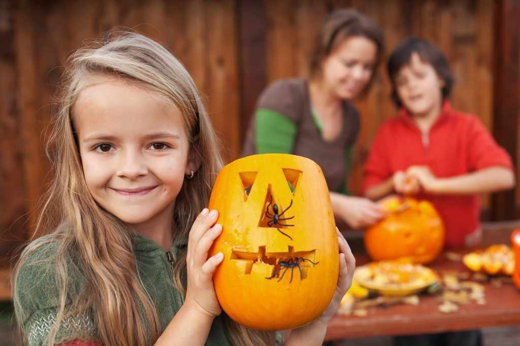 a little girl holds a jack-o-lantern pumpkin carved for Halloween with her family