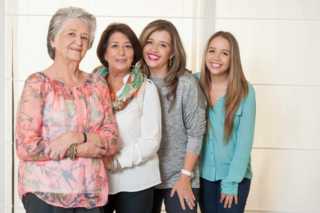 four generations of women, smiling, standing together and leaning against one another