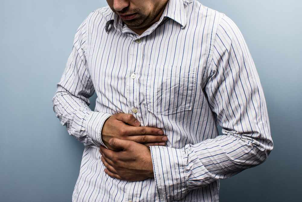 Multi-racial man with stomach pain