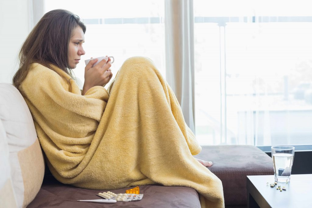 a woman wrapped in a blanket looking sick with cold or flu, holding a cup